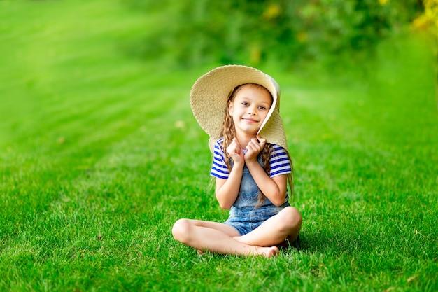 여름에 잔디밭에 있는 재미있는 아기 소녀는 녹색 잔디에 큰 밀짚 모자를 쓰고 재미있고 기뻐하며 문자를 보낼 수 있는 공간입니다.