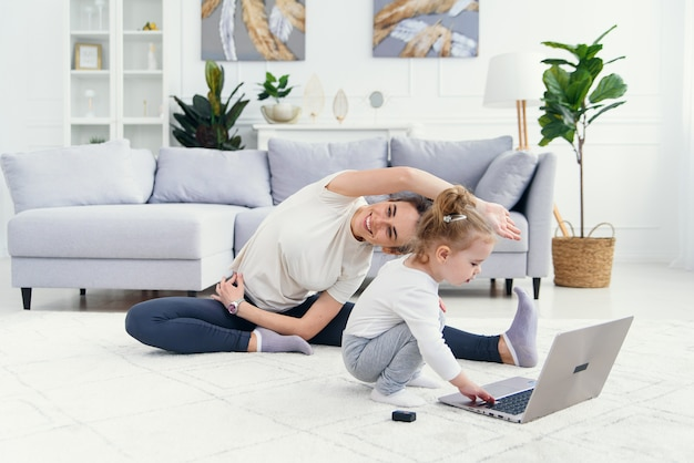 Funny baby girl playing with laptop while her sporty healthy mommy having online yoga training at home.