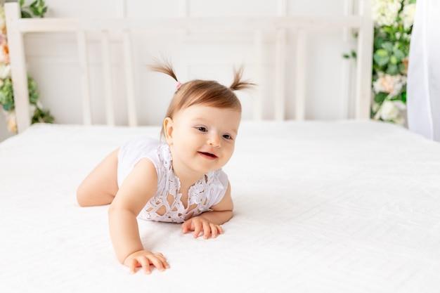 Смешная девочка шести месяцев ползет в яркой красивой комнате на белой кровати в кружевном боди и улыбается