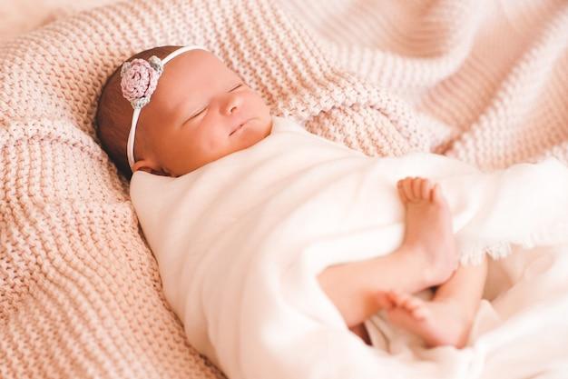 眠っていて、ベッドのクローズアップで夢を見ている面白い女の赤ちゃんおはよう子供時代
