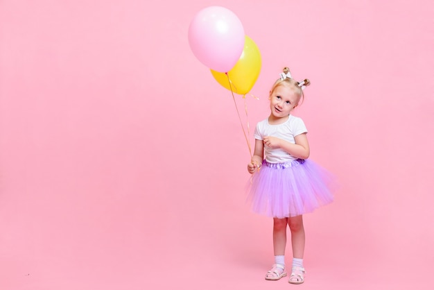 Funny baby girl in white t-shirt and lilac skirt with balloons on pink background. children's portrait with space for text.