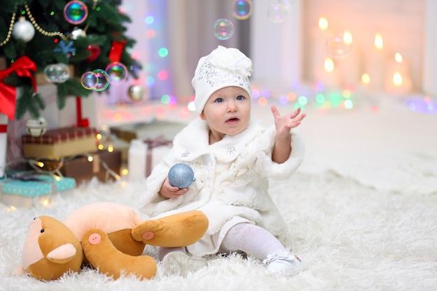 明るい背景の上のクリスマスツリーの近くにクリスマスおもちゃと面白い女の赤ちゃん