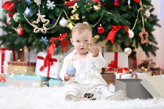 Смешная девочка с подарочными коробками и елкой на фоне