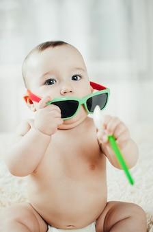 明るい部屋のベッドに座って、スプーンでサングラスで面白い赤ちゃん