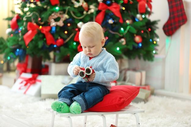 썰매와 크리스마스 트리와 벽난로에 앉아 재미있는 아기