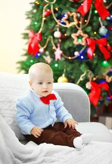 Забавный ребенок сидит на диване и елка на фоне
