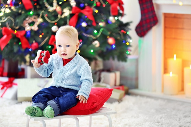 Funny baby  sitting on sledge and christmas tree and fireplace on