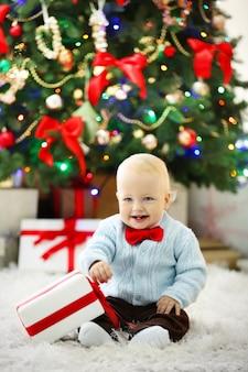 Забавный ребенок с подарочной коробкой и елкой на фоне