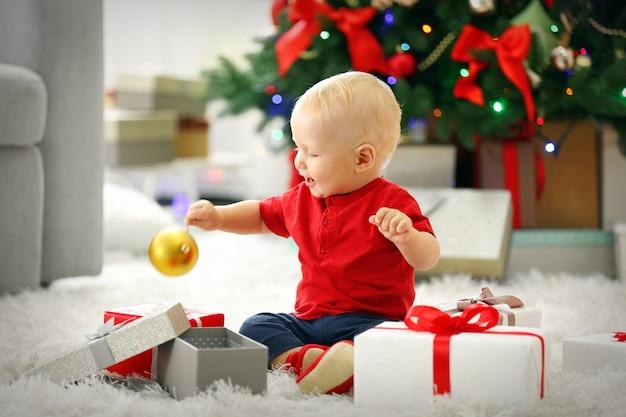 배경에 선물 상자와 크리스마스 트리가 있는 재미있는 아기