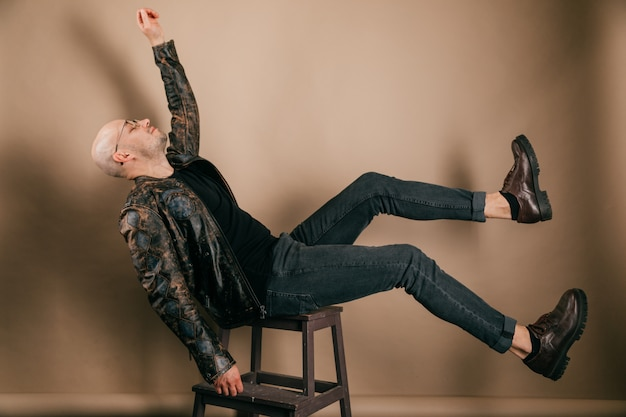 Funny bald man in biker leather jacket and oxford shoes. stylish weird boy falling down from chair.