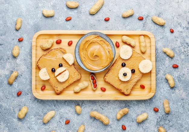 Смешной медведь и обезьяна лицо бутерброд с арахисовым маслом, бананом и черной смородиной, арахис, вид сверху