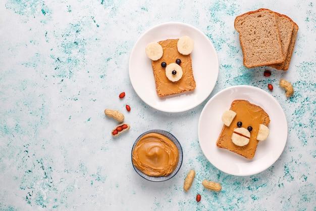 Смешной медведь и обезьяна лицо бутерброд с арахисовым маслом, бананом и черной смородиной, вид сверху