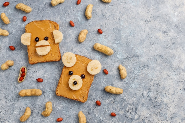 Funny bear and monkey face sandwich with peanut butter, banana and black currant, peanuts on grey concrete table, top view
