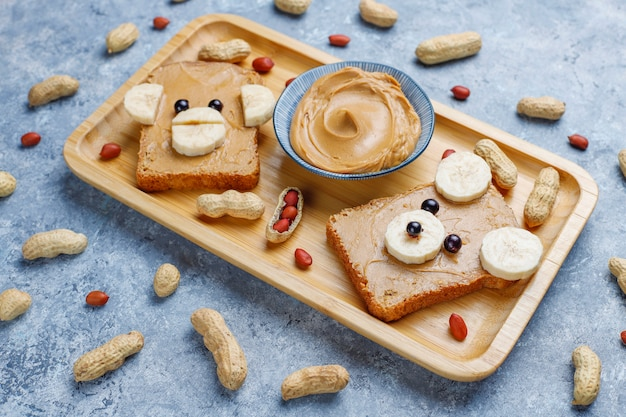Funny bear and monkey face sandwich with peanut butter, banana and black currant, peanuts, top view