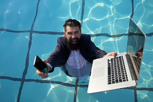 Funny bearded business man in suit using phone and laptop in swimming pool. concept of young people working mobile devices.