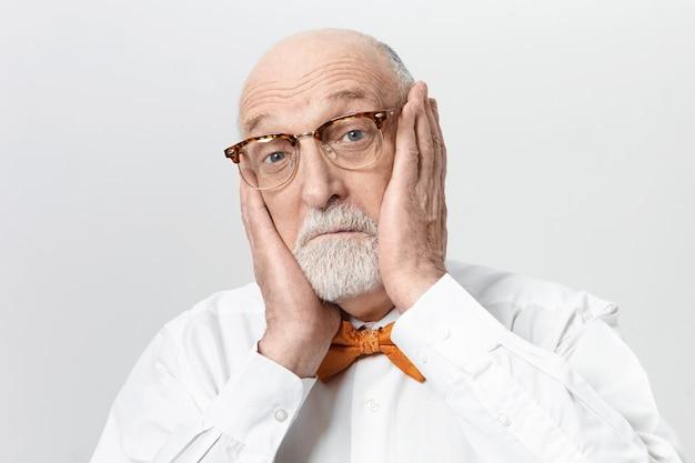 Uomo anziano barbuto divertente in occhiali alla moda che soffrono di un terribile mal di denti, tenendosi per mano sulle guance, scuotendo gli occhi azzurri. maschio anziano spaventato che esprime shock e stupore