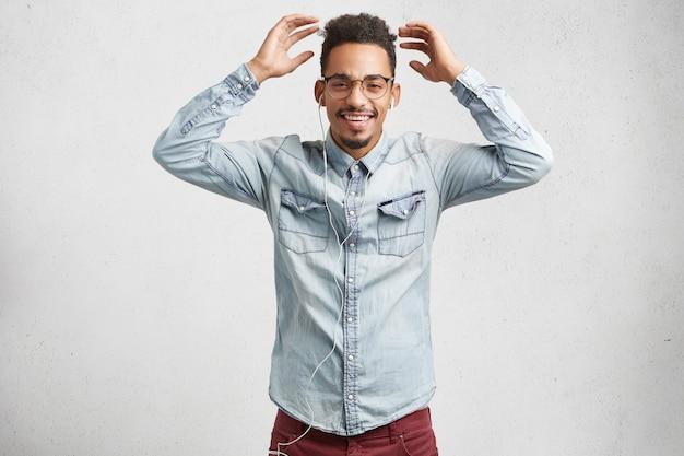 面白いひげを生やしたファッショナブルな男性はイヤホンで音楽を聴き、現代の電子機器を使用し、