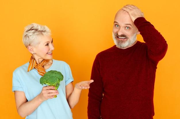 困惑した表情で胸に手をつないでいるおかしなひげを生やした男性年金受給者は、妻が彼に提供しているブロッコリーを食べたくない。
