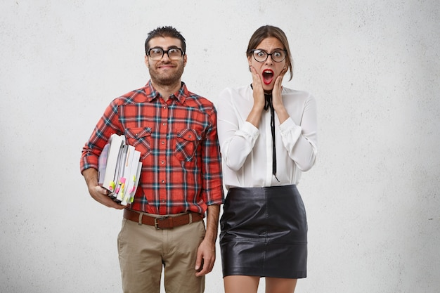 Funny bearded man in big spectacles with thick lenses keeps many books going to conduct lessons for pretty young woman