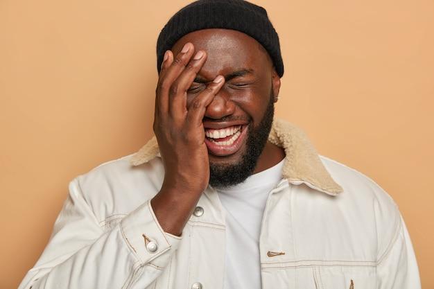 Забавный бородатый мужик закрывает половину лица, имеет зубастую улыбку, хихикает от анекдота