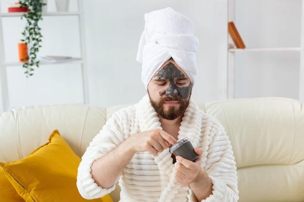 Забавный бородатый мужчина развлекается с косметической маской на лице из черной глины по уходу за кожей мужчин