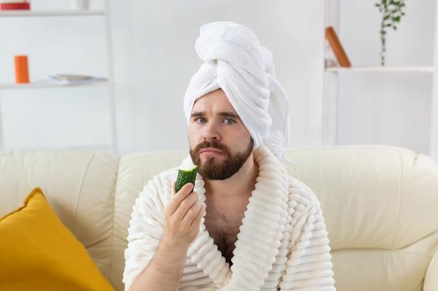 얼굴 스파에 오이 조각을 들고 있는 재미있는 수염 난 남자와 남성을 위한 피부 관리