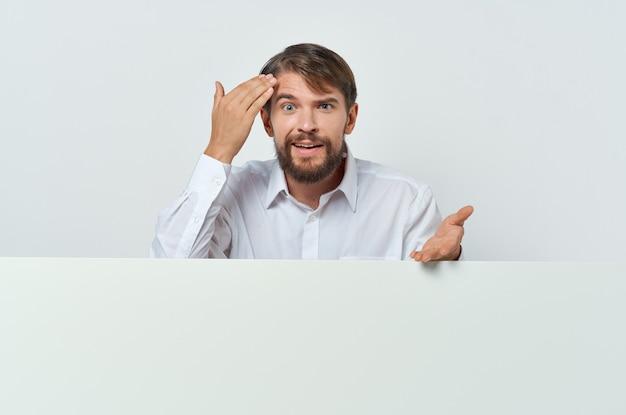 面白いひげを生やした男は、広告のプレゼンテーションの近くに立っています