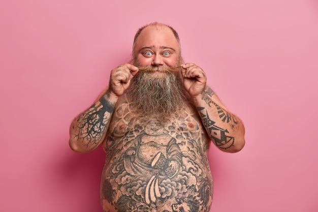 L'uomo barbuto divertente tocca i baffi, sta nudo con la grande pancia, il corpo tatuato, si diverte e parla con gli amici, posa contro il muro rosa. ragazzo obeso a torso nudo al coperto. persone, alimentazione, forma del corpo