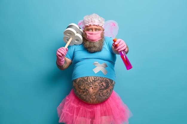 뚱뚱한 문신을 한 배를 가진 재미 있은 수염 난 남자는 요정 의상 보호 마스크를 착용하고 집 청소를위한 세제와 플런저를 보유하고 있습니다.