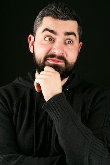 Funny bearded man with grey hair holds fingers on his chin