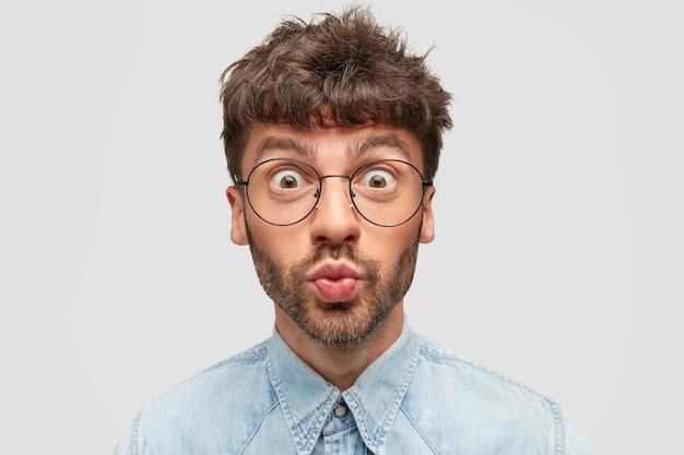 面白いひげを生やした若い男性は唇を丸めて目を飛び出し、漫画の表情をし、丸い眼鏡とデニムシャツを着て、不信を表現し、素晴らしいことに反応し、屋内に立っています