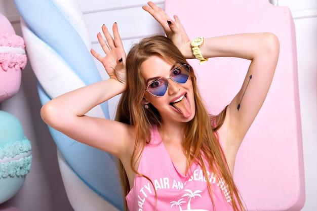大きなカラフルな偽のお菓子の壁にポーズをとって、しかめっ面をして、舌を見せて、面白い美しい狂った女性。明るい感情、流行のピンクの服、幸せなブロンドの女の子