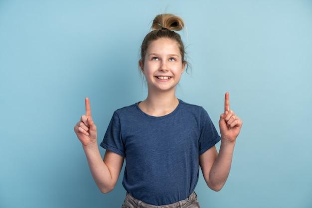 파란색 티셔츠에 재미있는 아름다운 소녀가 손가락을 보여줍니다.