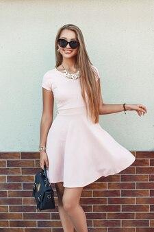 Смешная красивая девушка в розовом платье у стены