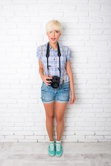面白い美しい女の子はカメラを持つフリーランスの写真家です
