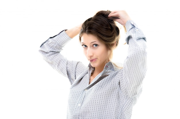 Funny beautiful girl with hairpin in her lips gathering hair up into a bun