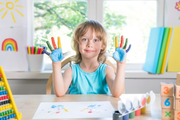재미있는 아름다운 행복한 아이는 페인트로 더러운 손을 보여줍니다. 페인트 선택적인 초점으로 웃고 있는 아이를 그립니다.