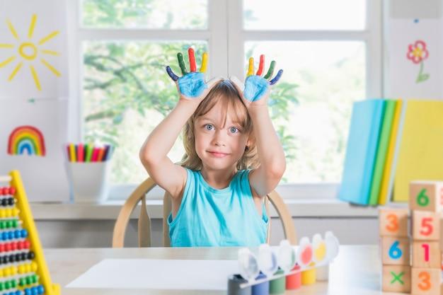 재미있는 아름다운 행복한 아이는 페인트로 더러운 손을 보여줍니다. 아이는 페인트로 웃고 있습니다.
