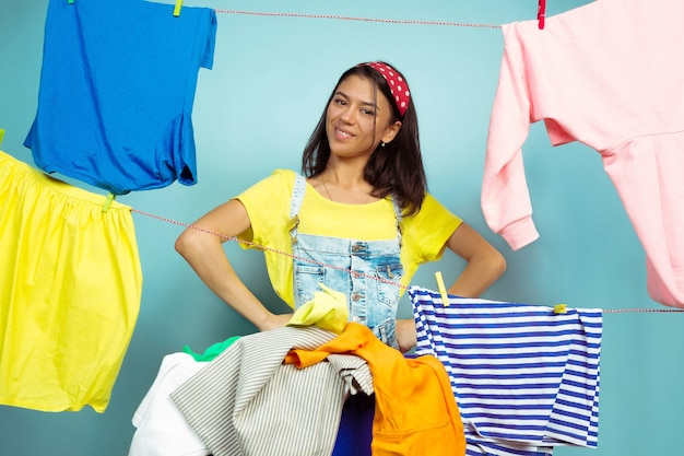 Funny and beautiful housewife doing housework isolated on blue background. young caucasian woman surrounded by washed clothes. domestic life, bright artwork, housekeeping concept. folding the laundry.