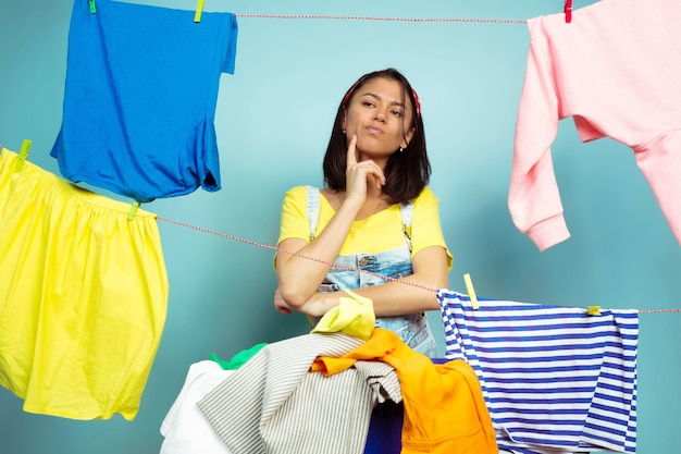 Casalinga divertente e bella che fa lavori domestici isolati su priorità bassa blu. giovane donna caucasica circondata da vestiti lavati. vita domestica, opere d'arte luminose, concetto di pulizia. piegare la biancheria.