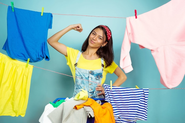 Funny and beautiful housewife doing housework isolated on blue background. young caucasian woman surrounded by washed clothes. domestic life, bright artwork, housekeeping concept. posing like hero.