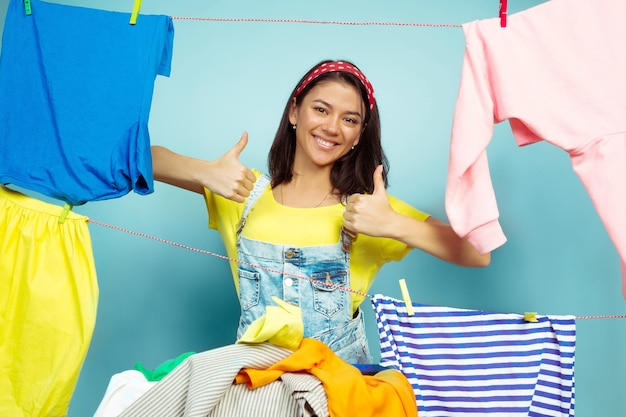 Funny and beautiful housewife doing housework isolated on blue space