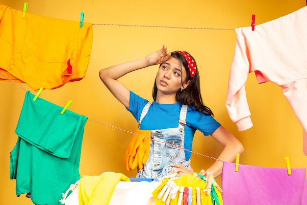 Funny and beautiful housewife doing housework isolated on yellow background. young caucasian woman surrounded by washed clothes. domestic life, bright artwork, housekeeping concept. sad and tired.