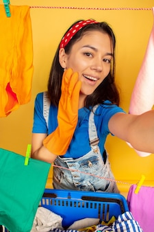 Funny and beautiful housewife doing housework isolated on yellow background. young caucasian woman surrounded by washed clothes. domestic life, bright artwork, housekeeping concept. selfie view.