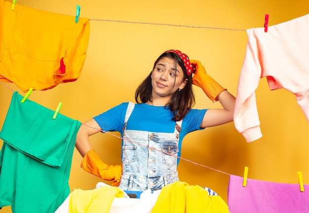 Funny and beautiful housewife doing housework isolated on yellow background. young caucasian woman surrounded by washed clothes. domestic life, bright artwork, housekeeping concept. uncertainty.
