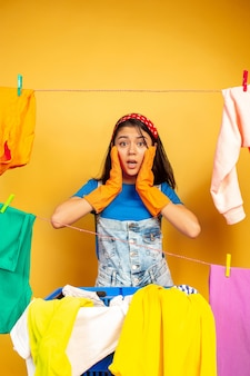 Funny and beautiful housewife doing housework isolated on yellow space. young caucasian woman surrounded by washed clothes