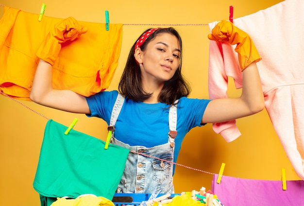Funny and beautiful housewife doing housework isolated on yellow space. young caucasian woman surrounded by washed clothes Free Photo