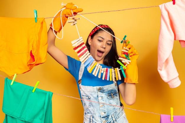 Casalinga divertente e bella che fa lavori domestici su priorità bassa gialla