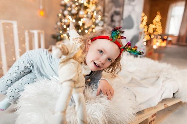 세련된 잠옷에 사슴 뿔을 가진 재미있는 어린 소녀가 침대에 누워 크리스마스 장식과 조명을 배경으로 장난감을 줍니다