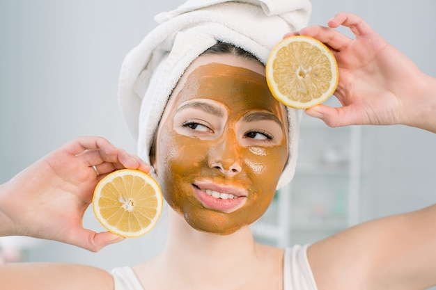 Funny beautiful model holding lemon slices up to her eyes. photo of girl with moisturizing brown facial mask. beauty and skin care concept